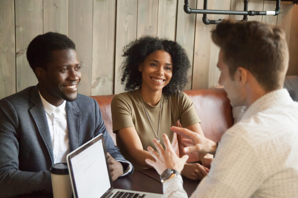 A young couple meeting with their broker to learn more about their down payment