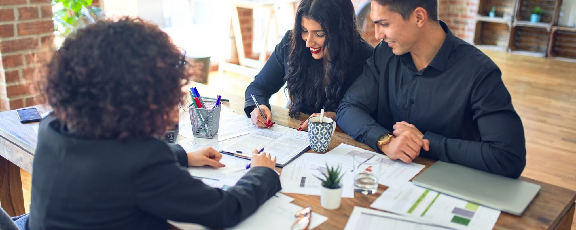 Young beautiful couple applying for mortgage. Sitting smiling happy meeting with real state agent signing mortgage loan at bank