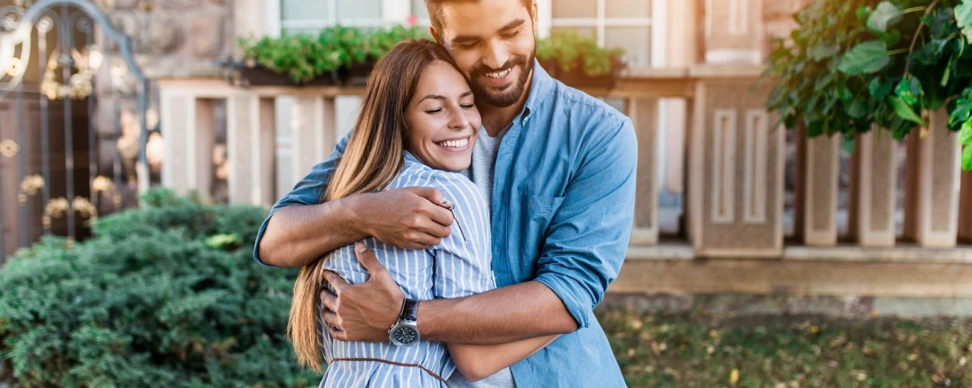 a young couple embracing outside their new home after they closed, becoming first time homeowners
