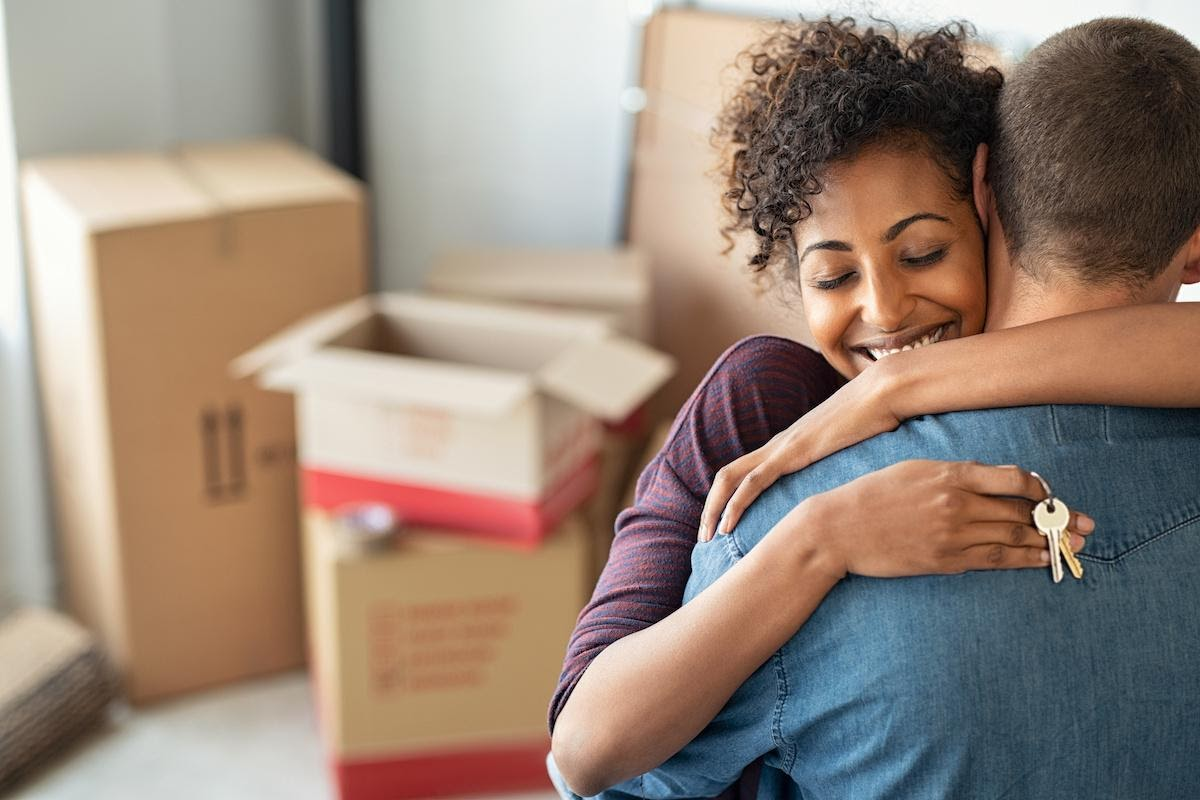A young couple embracing with moving boxes in the background