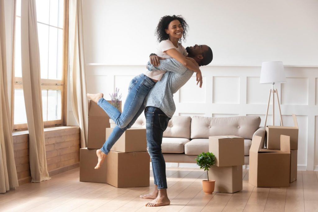 A happy young couple embracing in their new house